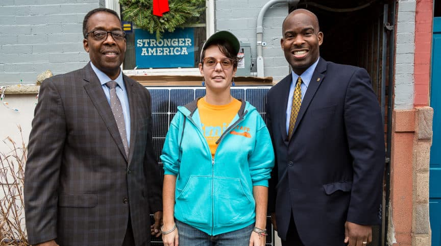 Council President Darrell Clarke and Councilmember Derek Green stand with Kate Zmich who had solar panels installed with Solarize Philly