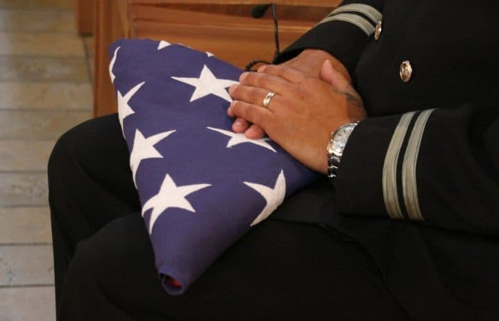 A close up of a folded US flag on a man's lap
