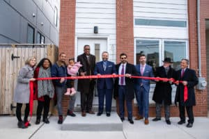 Council president Darrell Clarke holds a ribbon with others in front of a home at the Francisville Workforce Housing project