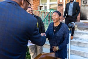 Council President Clarke shakes hands with a new homeowner