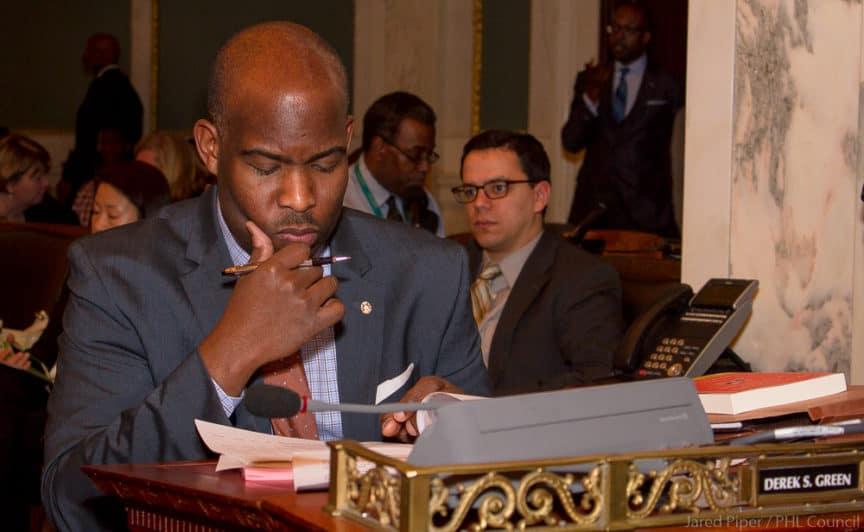 councilmember Derek Green reading a document