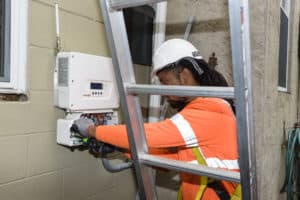 Solar panel technician working on an electrical panel