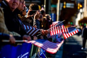 Onlookers wave US flags at the Veterans' Day Parade